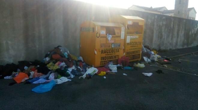 rifiuti fuori dal cassonetto della caritas